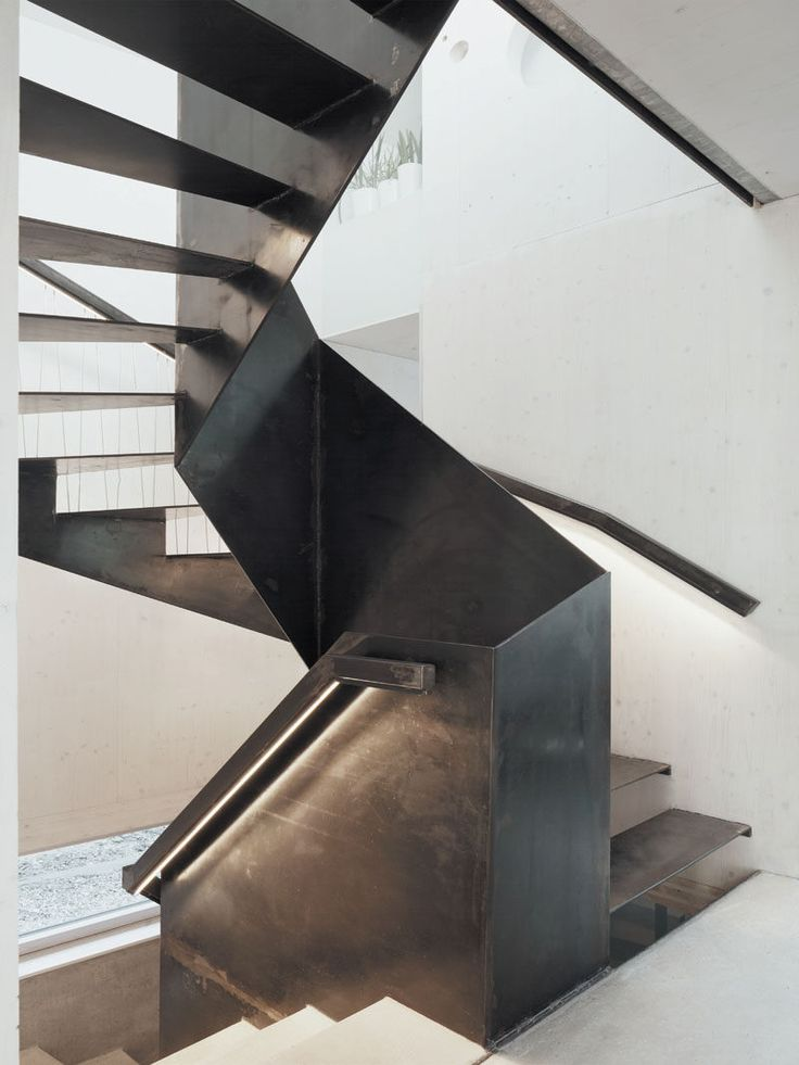 Black steel stairs and handrails continue to lead you up to the upper floor of this modern home.