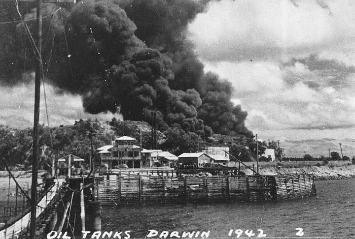 black+white photo - damage from Japanese bomb attack to oil storage site, Stokes Hill, above Darwin harbour, Northern Territory 1942. There are 2 plumes of smoke billowing, indicating 2 large oil tanks have been hit. On the left side is a temporary suspension bridge, linking 2 parts of the Stokes Hill wharf, damaged in a previous attack. The building with columns in the centre is Darwin's Flying Boat Base.  ©the National Archives of Australia www.naa.gov.au/
