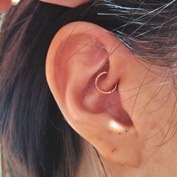 Fresh daith piercing with a 14k rose gold clicker by Maria Tash