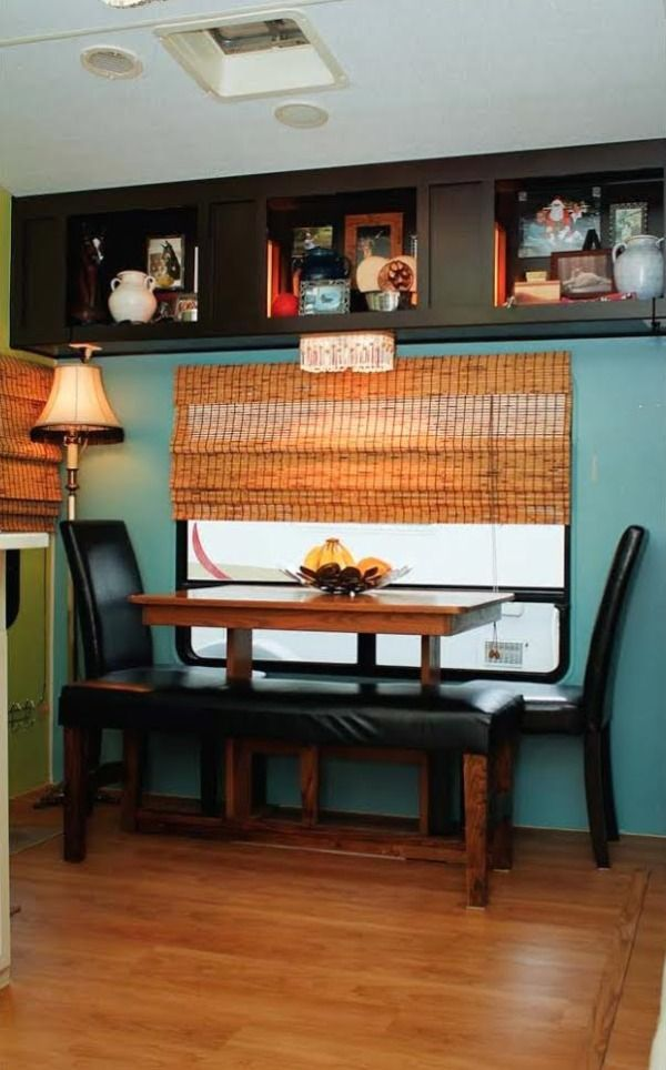 Couple Renovate 5th Wheel Travel Trailer into Tiny Home Photo.  LOVE the display cubbies, the fantastic crystal light fixture, fiber roman shades, comfy seats, walls are a beautiful color!