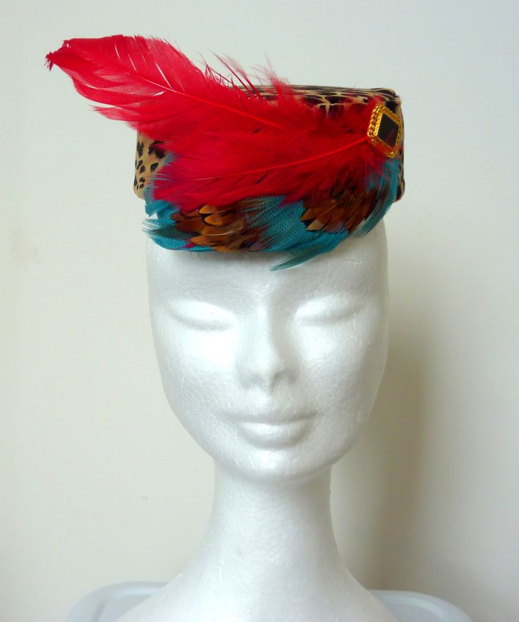 Cocktail hat leopard print/race hat leopard. Pillbox hat leaopard print, red feathers and teal feather with black and gold rectangular embelishment