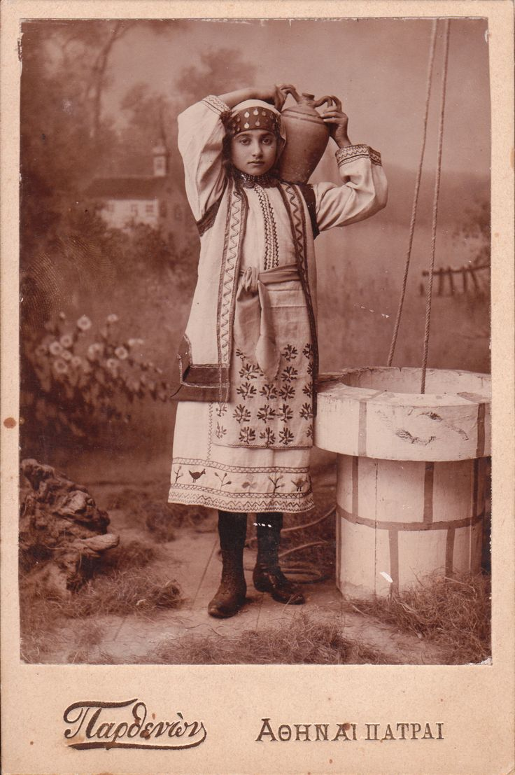 This cabinet card features a girl in traditional Greek clothing posing by a well.