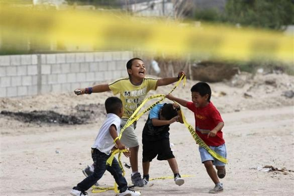 Children play with police tape at a crime scene in Rancho Anapra neighborhood in Ciudad Juarez July 22, 2012. Two people were killed and another injured after a gang fight where the assailant allegedly used a baseball bat to attack victims, according to local media  REUTERS/Jose Luis Gonzalez