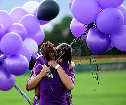 Friends of shooting victim AJ Boiks gather and comfort each other at Gateway High School before a vigil in his honor where they dressed in his favorite color, purple, and released purple balloons on Saturday, July 21, 2012 in Aurora, Colo.