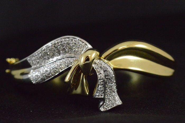 18 karaat bicolour strik armband met hoge kwaliteit diamanten  De chique armband is van 18 karaat geelgoud en witgoud gemaakt. De armband heeft een vorm van een strik die rijk bezaaid is met briljant geslepen diamanten. Diamant (ca. 80 stuks)Slijpvorm: Briljant Gewicht: 160 karaat Kleur: F-G Zuiverheid: VVS Slijpkwaliteit: Very Good JuweelGewicht: 31.9 gram Diameter: 5.8 - 49 cm Keurmerk: 18 karaat (750)- Wordt gestuurd in een sieradendoosje. - Tijdens de veilingdagen is dit kavel te…