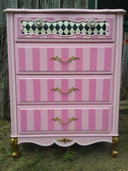 This is a Ditsy Chick original. Handpainted upcycled chest of drawers from french provencial. I never know what the finished design will be, but I did know that it needed to be pink with black harlequin on the sides. The gold leaf gives it a great tah dah! Although this is very sturdy furniture thats in great condition, it is upcycled. There are 3 imperfections. I was able to add two of them in the photos...the back leg and two small places on the top laminate. Please convo me before…