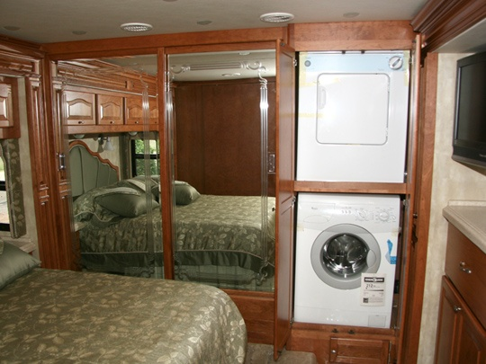 Rv bedroom with washer dryer in a closet in the bedroom next to a closet with mirrored doors - Trailer bedroom ideas ...