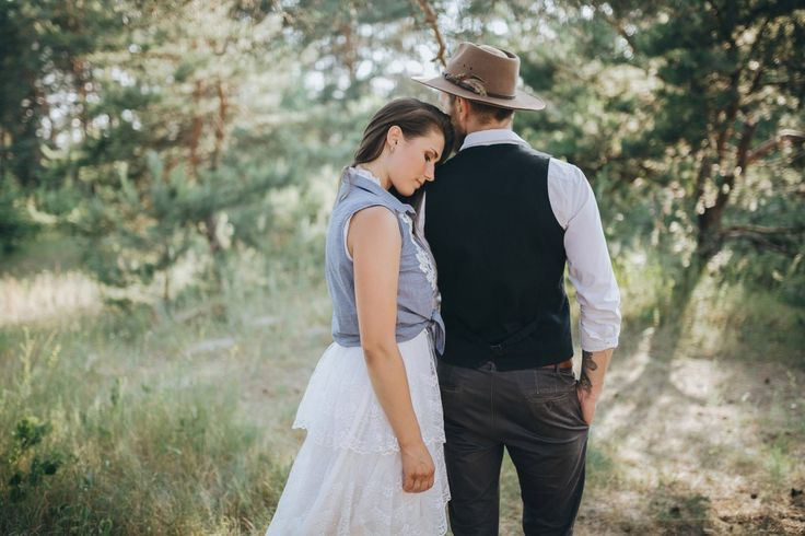 woman in a wedding dress and a bearded man in a waistcoat and hat stand in a clearing in the pine forest