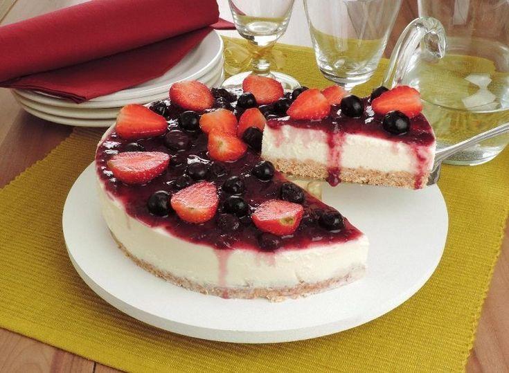 Na foto, o cheesecake de frutas vermelhas está em uma travessa redonda de vidro branca. A sobremesa tem uma fatia cortada revelando as camadas de massa, recheio e cobertura. O doce está decorado com morangos e mirtillos. A mesa está com uma toalha amarela e na decoração estão copos, talheres e pratos.