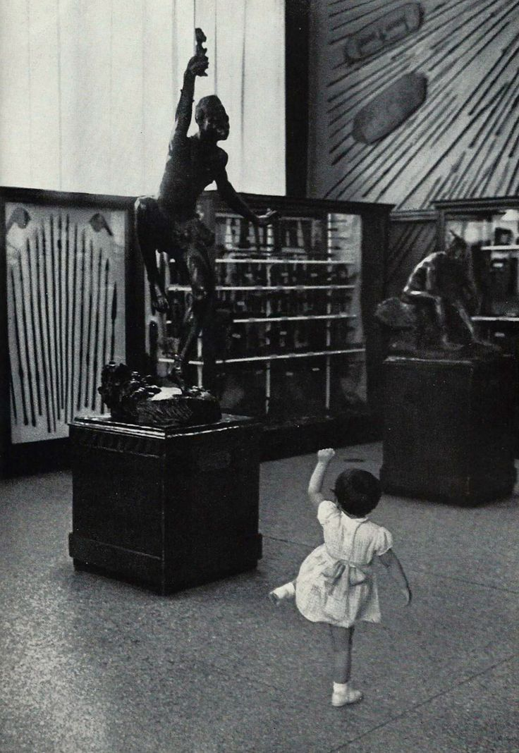 A child at the Smithsonian Institution dances in empathy with a bronze witch doctor statue National Geographic | June 1960