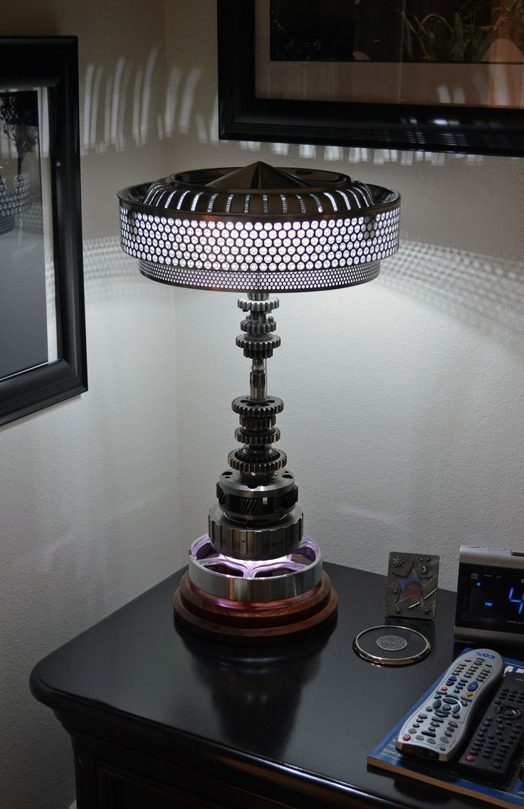 Gear shaft lamp, made using gear clusters from a motorcycle, and other parts from both Ford and Chevy transmissions. Shade is a mid-60's Plymouth hubcap with a Mercedes air cleaner mesh, and a smaller inside ring made from aluminum perforated mesh. 12V automotive LED bulbs and an LED strip inside the planetary gear housing. Bubinga base.