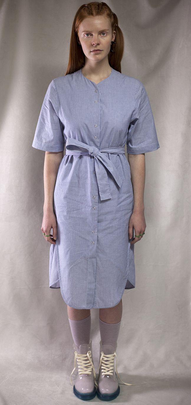 Alix porte la robe chemise CODE.   Robe, coupe ample, serrage par ceinture du même tissu, boutons pression en métal. Longueur sous le genou. 100% coton.