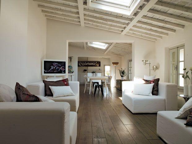 In salotto, divani su disegno rivestiti con tessuto di cotone operato. PARQUET in rovere a listoni lasciato al naturale e trattato a cera