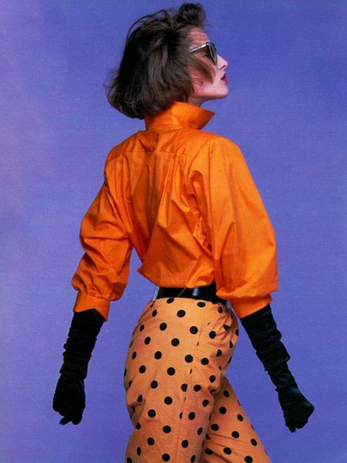 mode année 80 en orange pantalon à pois noirs et chemisier manches chauve souris col haut
