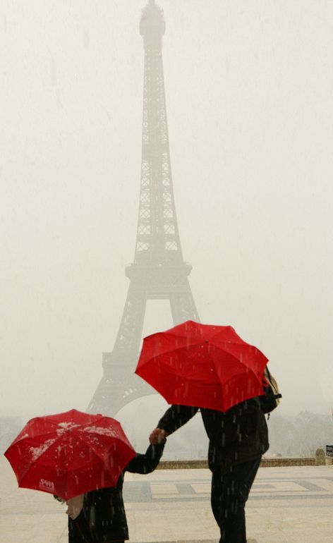 Red Umbrellas at the Eiffel Tower during a hailstorm.
