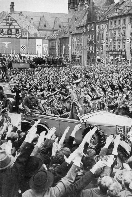 October 1938: Hitler is driven through the crowd in Cheb (German: Eger), in the German-populated Sudetenland region of Czechoslovakia, which had been annexed to Nazi Germany as part of the Munich Agreement