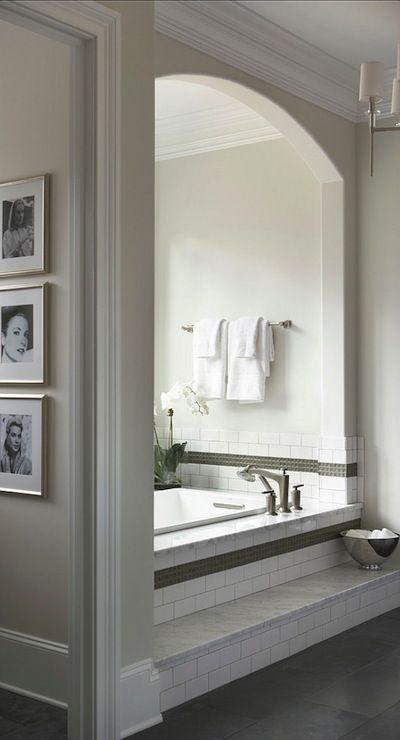 Linda McDougald Design - bathrooms - arched bath nook, bath nook, step to bath, steps to bath, drop-in bath, soaking tub, glazed pocelain tile, glazed porcelain tile surround, green mosaic tile, green mosaic tiled border, marble ledge, marble step, greige walls, greige wall color, polished nickel towel rail, fresh white towels, white towels, orchid, silver framed art, silver framed photography, framed black and white photography, white tile bath surround, white porcelain tile bath surround…
