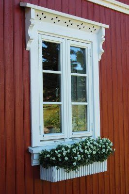 White window with flowers on old red country house