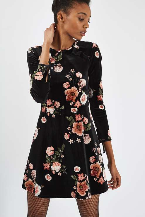 No doubt this season's biggest trend, the velvet dress has arrived in floral form. In a figure-flattering flippy style, it comes finished with pretty frill neck detail. #Topshop