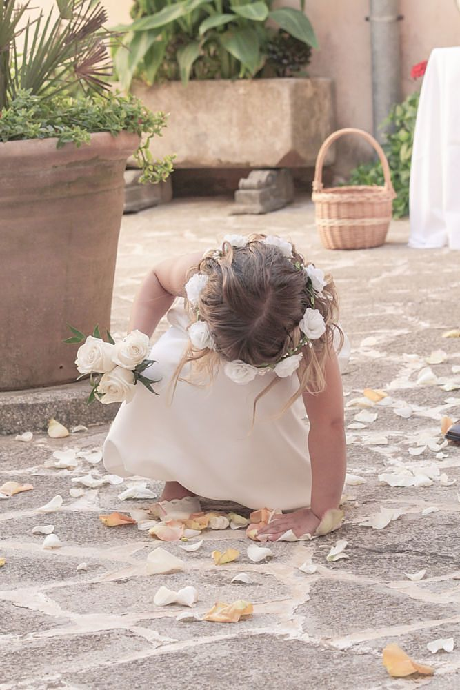 The little bridesmade picking up rose petals for her basket. The foto is from a norwegian wedding i Majorca in Juli 2014.