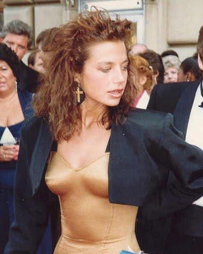Justine Bateman circa 1987 in a skin tight gold dress, huge gold cross earrings, and big 80's hair