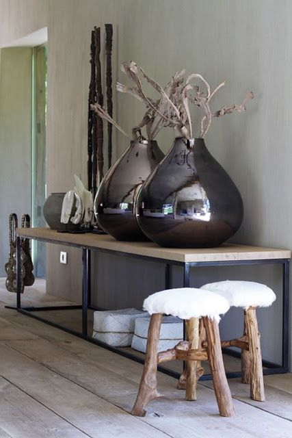 Extra large vessels with natural wood creates an intriguing table top vignette