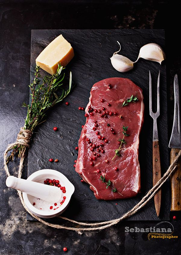 Raw striploin beef steak on black background - Raw fresh meat Striploin steak and seasoning on blackslate board over dark metal background, top view