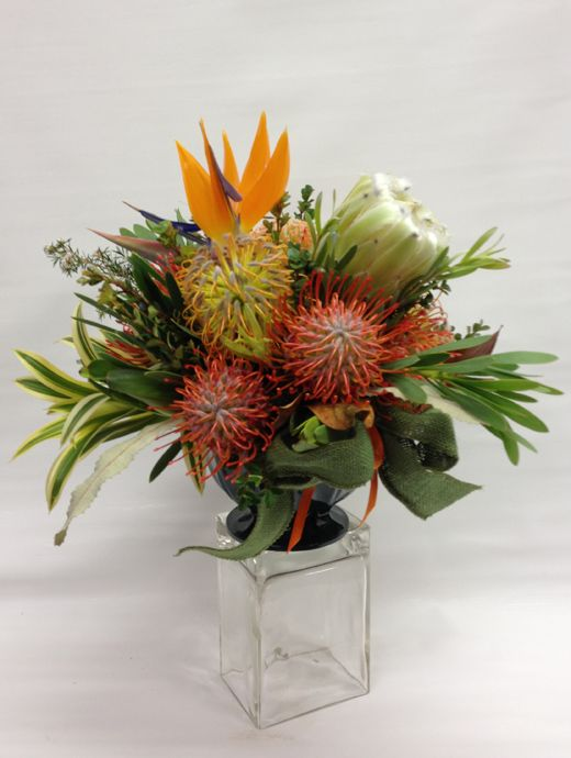 Paradise in Bloom Thanksgiving Arrangement. We've gathered our finest flowers to brighten your harvest table. We start with a luscious Bird of Paradise and surround it with a spectacular arrangement of Pincushions, a downy soft Mink Protea and various greenery. This great Thanksgiving centerpiece is presented in our special pedestal-base bowl.