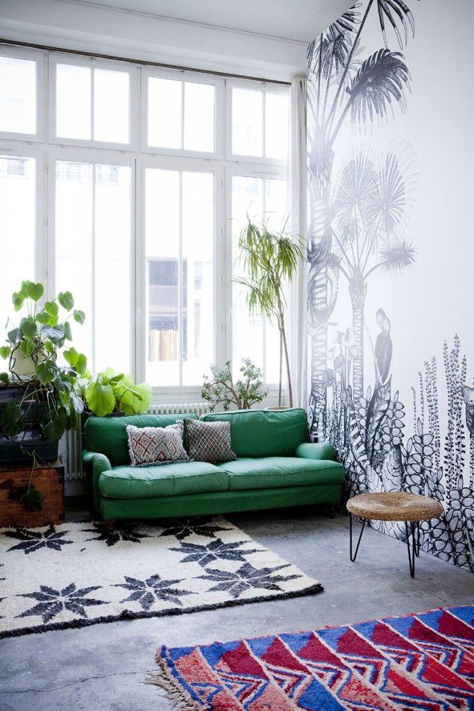 Un paysage fleuri au mur et un canapé intense dans le salon
