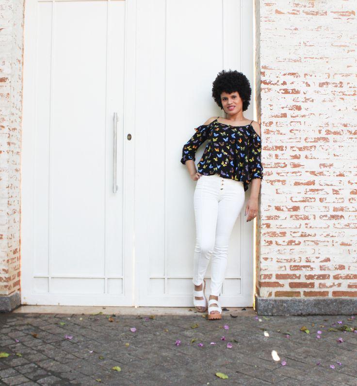 Look da Jane com blusa estampada de borboletas e recorte nos ombros combinada ao jeans branco da Colcci.