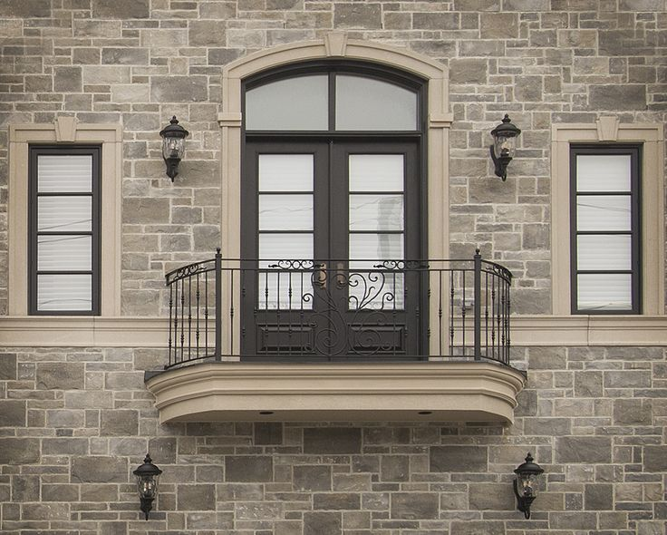 Now that's one beautiful balcony - built with stone around the double black doors.