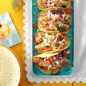 Fantastic Fish Tacos--	1/2 cup fat-free mayonnaise..  	1 tablespoon lime juice...  	2 teaspoons fat-free milk...  	1/3 cup dry bread crumbs...  	2 tablespoons salt-free lemon-pepper seasoning...  	1 egg...  	1 teaspoon water...  	1 pound mahi mahi or cod fillets, cut into 1-inch strips...  	4 corn tortillas (6 inches), warmed...TOPPINGS:,  	1 cup coleslaw mix..  	2 medium tomatoes, chopped..  	1 cup shredded reduced-fat Mexican cheese..   	1 tablespoon minced fresh cilantro