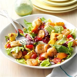 1/3 cup orange juice 3 tablespoons cider vinegar 1-1/2 teaspoons Dijon mustard 1-1/2 teaspoons honey 1 tablespoon minced fresh tarragon SALAD: 4 teaspoons canola oil, divided 1 cup fresh or frozen corn 1 pound uncooked shrimp (26-30 per pound), peeled and deveined 1/2 teaspoon lemon-pepper seasoning 1/4 teaspoon salt 8 cups torn mixed salad greens 2 medium nectarines, cut into 1-inch pieces 1 cup grape tomatoes, halved 1/2 cup finely chopped red onion