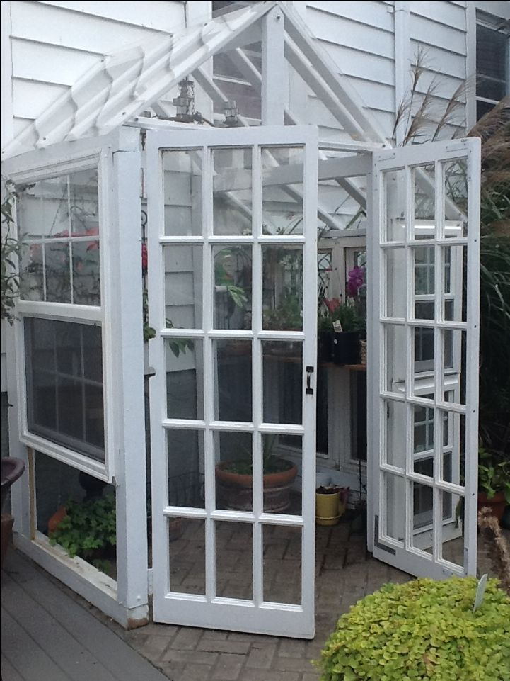 Greenhouse made from recycled windows and doors with reclaimed wood.