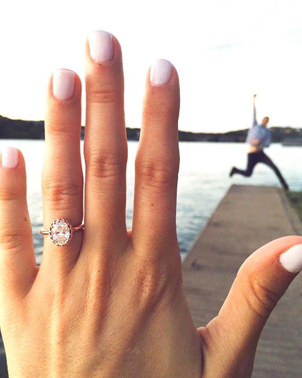 Chica mostrando su anillo de compromiso mientras que su novio salta al fondo de un muelle