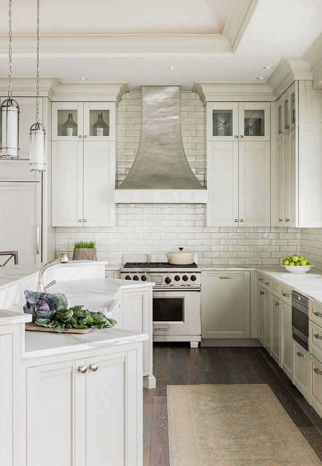 hood. Ivory Kitchen. Ivory Kitchen Cabinet Paint Color. Ivory Kitchen Cabinets. Kitchen with ivory cabinets paired with white marble countertops and a glazed ivory subway tiled backsplash. #IvoryKitchen #IvoryKitchenPaintColor