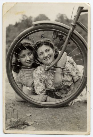 Jewish sisters pose behind a bicycle wheel where they are recuperating in Sweden