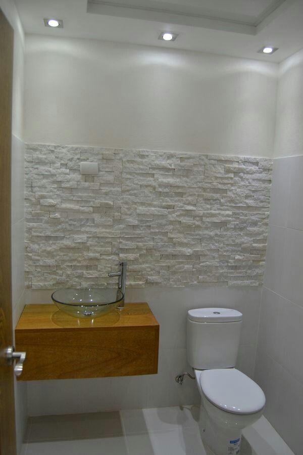 Baño de visitas con piedras decorativas y lavamanos con base de roble