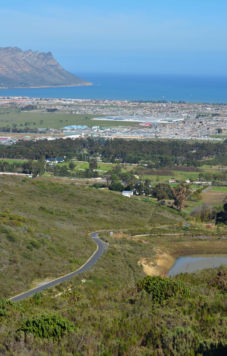 The road down from Scapenberg (on Waterkloof Wine Estate) in Somerset West - False Bay and Gordons Bay visible on horison - Helderberg area of Cape Town. #somersetwest #schapenberg #capetown #waterkloofwineestate #waterkloof