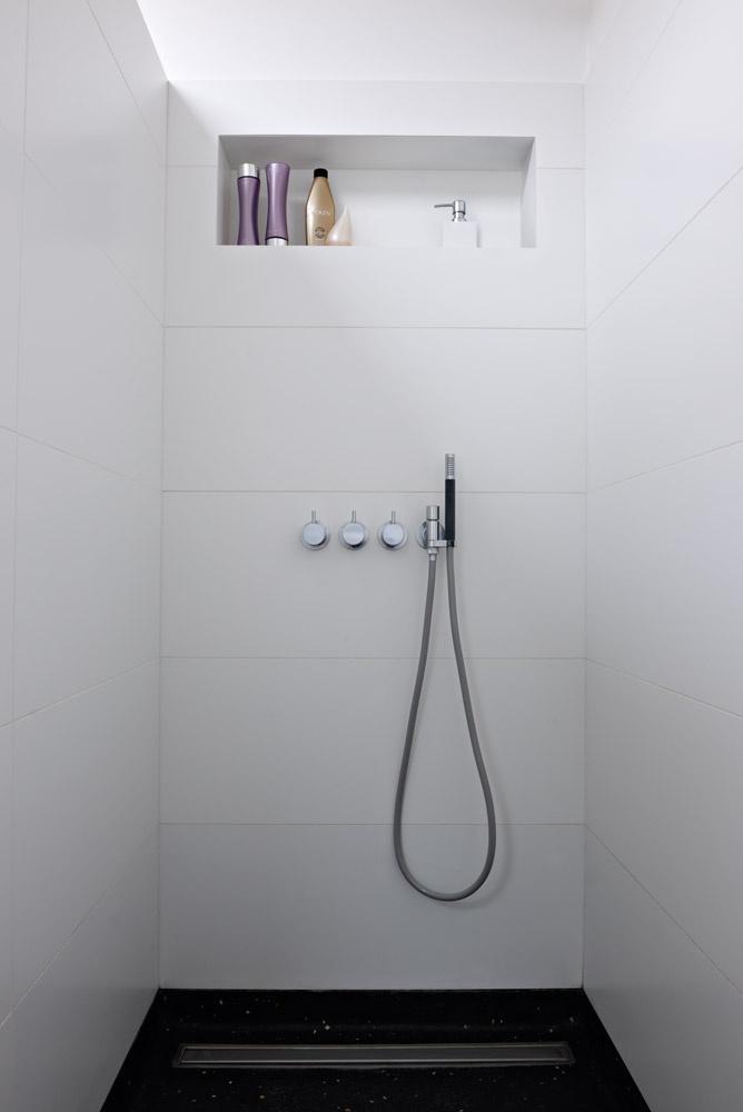 [+] revestimento claro, nicho para utilidades embutido, sem saliências em caso de acidente, ralo do tipo grelha. [-] falta de ducha no teto, aparenta ser chuveiro tipo europeu...