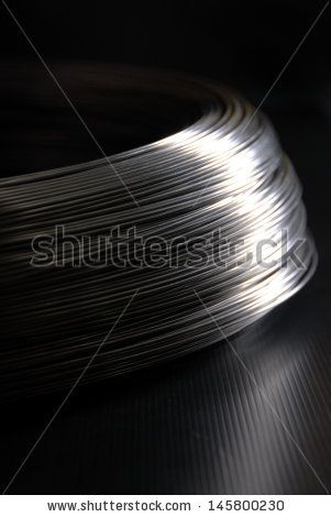 Steel wire in a coils on the dark background vertical - stock photo