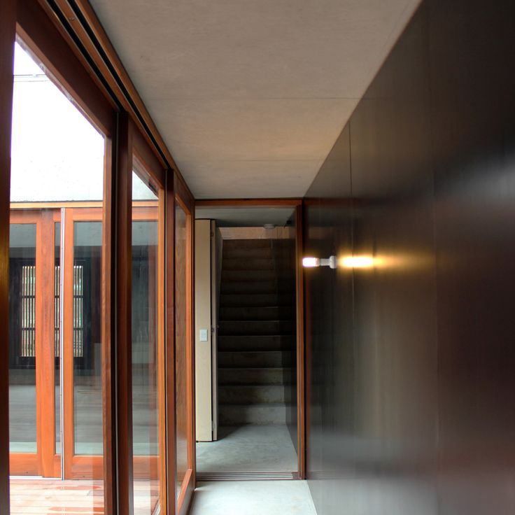 Hallway, alfresco courtyard, glass sliding doors, timber sliding doors, concrete, concrete roof, concrete floor, concrete stairs, black walls, extensions and renovations, architectural details, Builder, NSW, Sydney, Northern Beaches, Avalon, askerrobertson design and construction