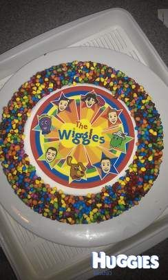 Chocolate mud cake, with a Wiggles cake decoration surrounded by coloured choc bits.