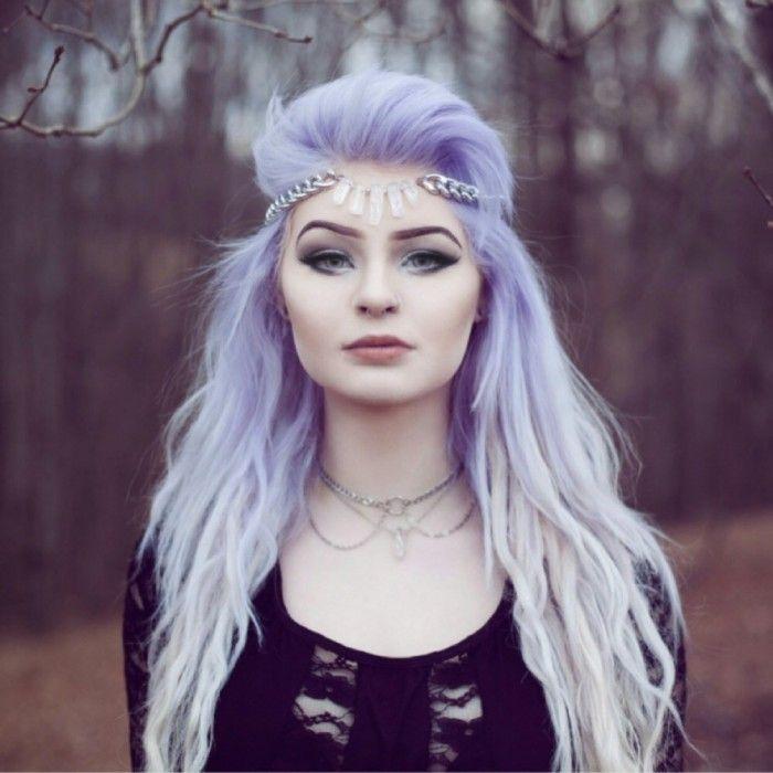 Chica con el cabello lila parada en un bosque