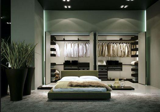 Este es el dormitorio. Hay una cama matrimonial, dos plantas, un espejo, dos armarios, una gran alfombra, dos luces lateral y cuatros luces sobre los armarios.