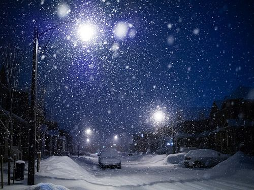 Snowy night. Snow flakes in the street lights.