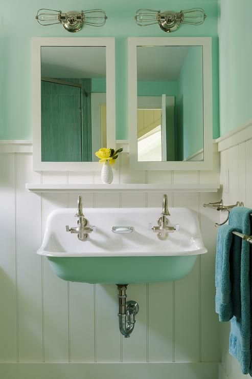Cottage bathroom with turquoise painted upper walls and vertical shiplap lower walls lined with a Kohler Brockway Sink painted turquoise and a floating shelf under a white parsons mirror illuminated by nautical cage wall sconces.