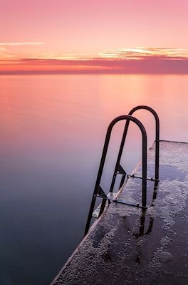 Amazing sunset at a pier by at Gotland, very warm colors reflecting in the ocean. Photograph by Sami Rahkonen, available as poster at printler.com, the marketplace for photo art.