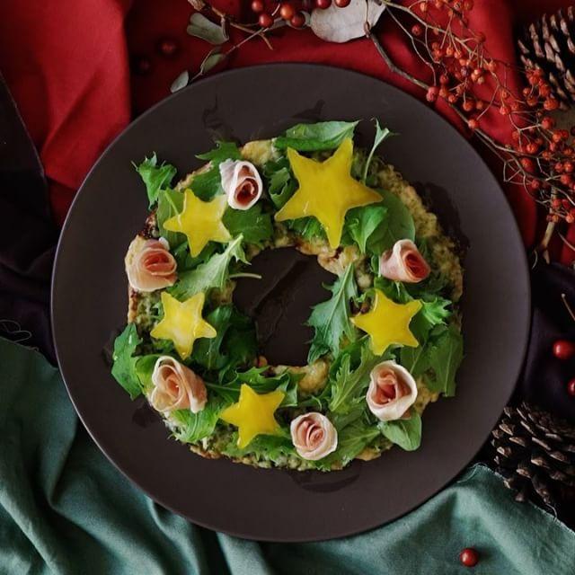 【キラキラ星の⭐️】クリスマスリースサラダピザ🍕 ■材料 ・ピザ生地(直径約17cm) 1枚 ・ジェノベーゼソース 大さじ2 ・ピザ用チーズ 大さじ3 《飾り》 ・オリーブオイル 大さじ1 ・生ハム 25g ・ベビーリーフ 10g ・黄パプリカ 1個 ■手順 【事前準備】 パプリカは星型でくり抜く。生ハムは横半分に切り、端から巻いてお花の形にする。  1. ピザ生地は真ん中をセルクルでくり抜く。 2. 1のピザ生地ジェノベーゼソースを塗り、ベーコンとピザ用チーズをのせて250度のオーブンで6〜7分焼く。 3. 焼きあがったピザにベビーリーフとお花の生ハム、星型のパプリカを彩りよく飾り、オリーブオイルをかける。 #おうちカフェ #料理 #cooking #レシピ #recipe #food #おうちご飯 #おうちごはん #昼ごはん #ランチ #晩ごはん #夜ごはん #ディナー #クリスマス #リース #サラダ #ピザ #星
