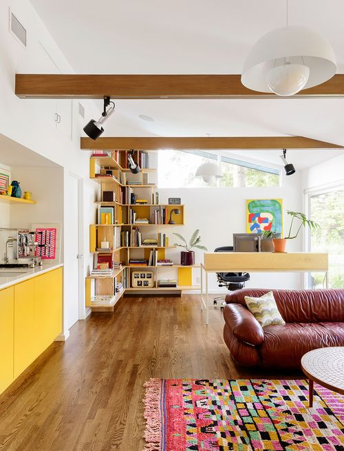 Colorful home office living space in midcentury modern home - love the yellow built in cabinets, comfy leather sofa, patterned rug, and wood beams